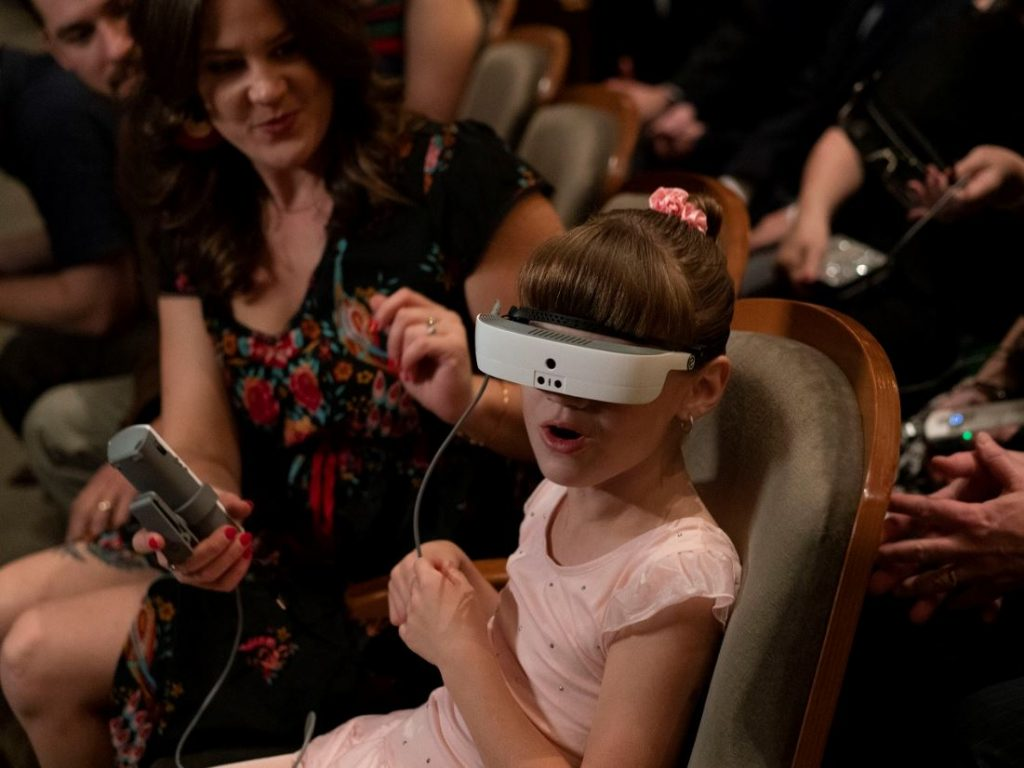 A little girl with low vision wearing eSight device