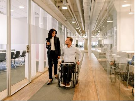 a guy on a wheelchair talking to a woman in the office