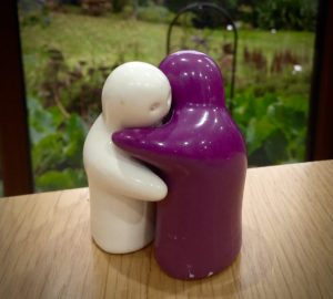 Purple and white salt and pepper hugging each other