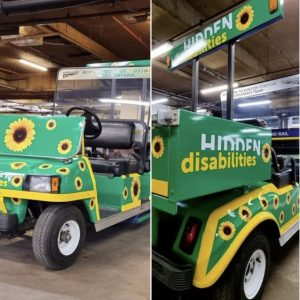 Image of the assistance buggy wrapped in 'Hidden Disabilities' branding