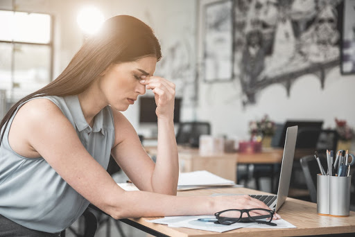 A girl sitting at her desk and holding her forehead